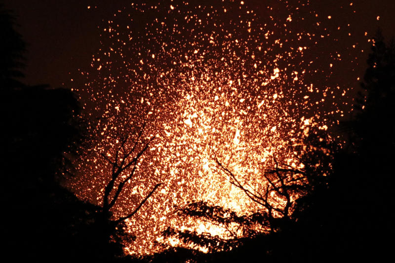 Lava erupts in the Leilani Estates subdivision near Pahoa, Hawaii Friday, May 18, 2018. Hawaii residents covered their faces with masks after a volcano menacing the Big Island for weeks exploded, sending a mixture of pulverized rock, glass and crystal into the air in its strongest eruption of sandlike ash in days. (AP Photo/Jae C. Hong)
