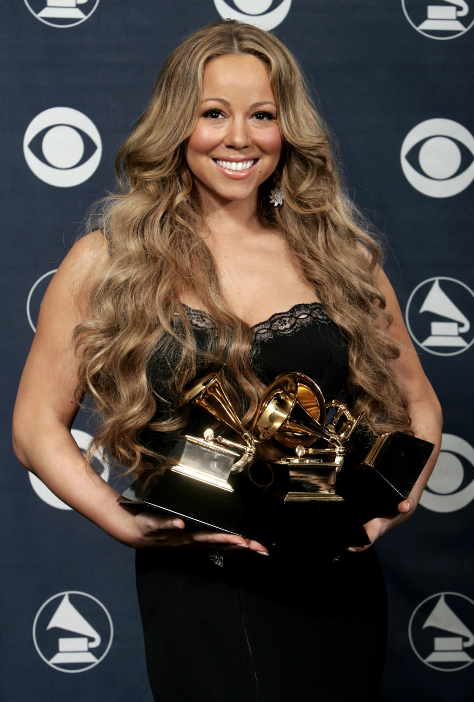 """FILE - Mariah Carey holds her three Grammy's for, best female R&B vocal performance, best contemporary R&B album, and best R&B song at the 48th Annual Grammy Awards in Los Angeles on Feb. 8, 2006. Johnta Austin worked with Mariah Carey on the hit song """"We Belong Together."""" (AP Photo/Reed Saxon, File)"""