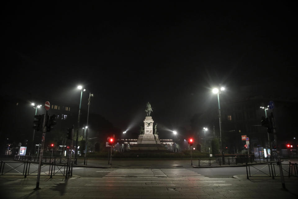 The statue of Italian patriot Giuseppe Garibaldi is lit in the middle of an empty square, in Milan, northern Italy, early Sunday, Oct. 25, 2020. Since the 11 p.m.-5 a.m. curfew took effect last Thursday, people can only move around during those hours for reasons of work, health or necessity. (AP Photo/Luca Bruno)