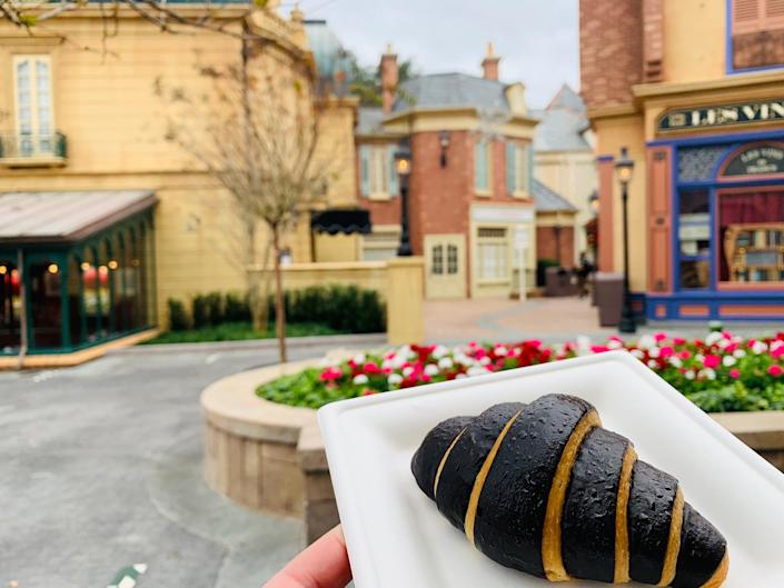 hand holding a pastry in front of the france pavilion at epcot