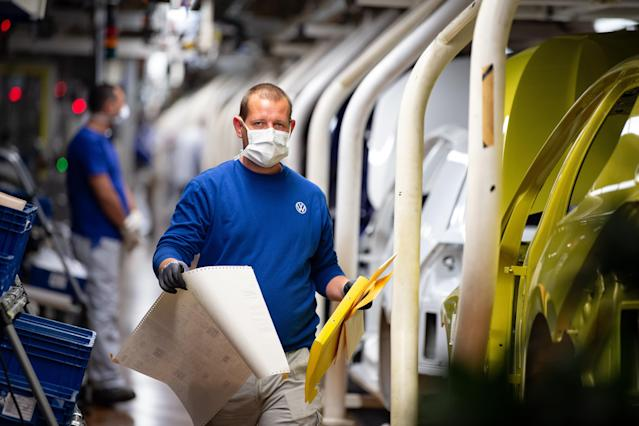 Volkswagen production line staff wear masks as they work at the Wolfsburg plant in Germany. (Swen Pförtner/Getty Images)