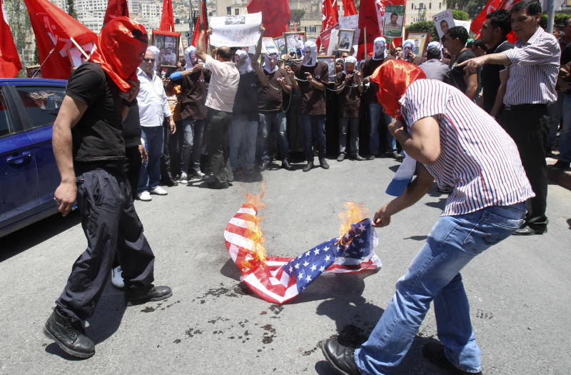 Palestinians burn an American flag during a rally to demand better conditions for Palestinian prisoners in Israeli jails, in Nablus, West Bank, Saturday, May 12, 2012. (AP Photo/Nasser Ishtayeh)