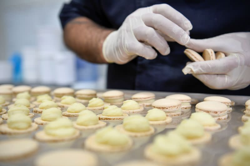 A worker prepares a macaron at the workshop of Belgian chocolate maker Marcolini, in Brussels