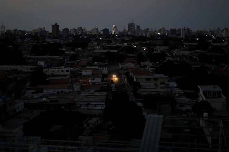 A car's headlights are seen in a neighborhood during a blackout in Maracaibo, Venezuela. (Photo: Ueslei Marcelino/Reuters)