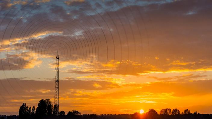 Radio waves escaping from gsm tower   visualisation at sunset in rural area.