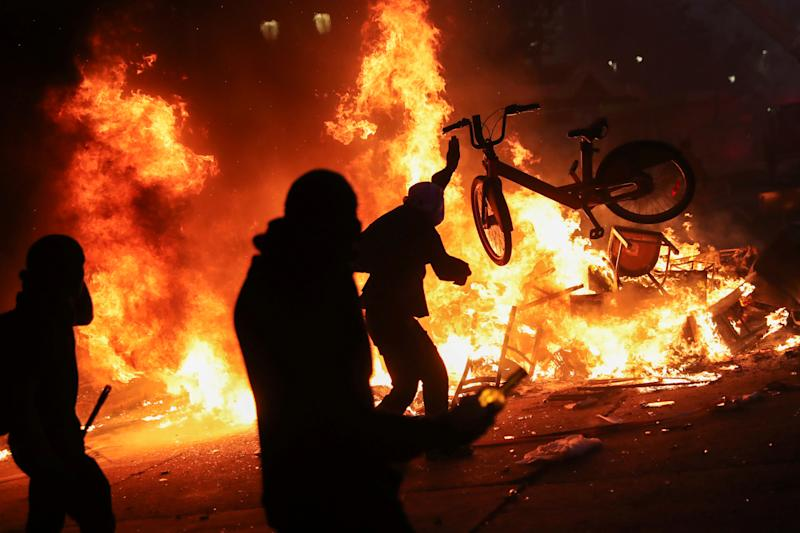 A demonstrator tosses a bicycle into an improvised bonfire during an anti-government protest in Santiago, Chile on Oct. 28, 2019. (Photo: Edgard Garrido/Reuters)