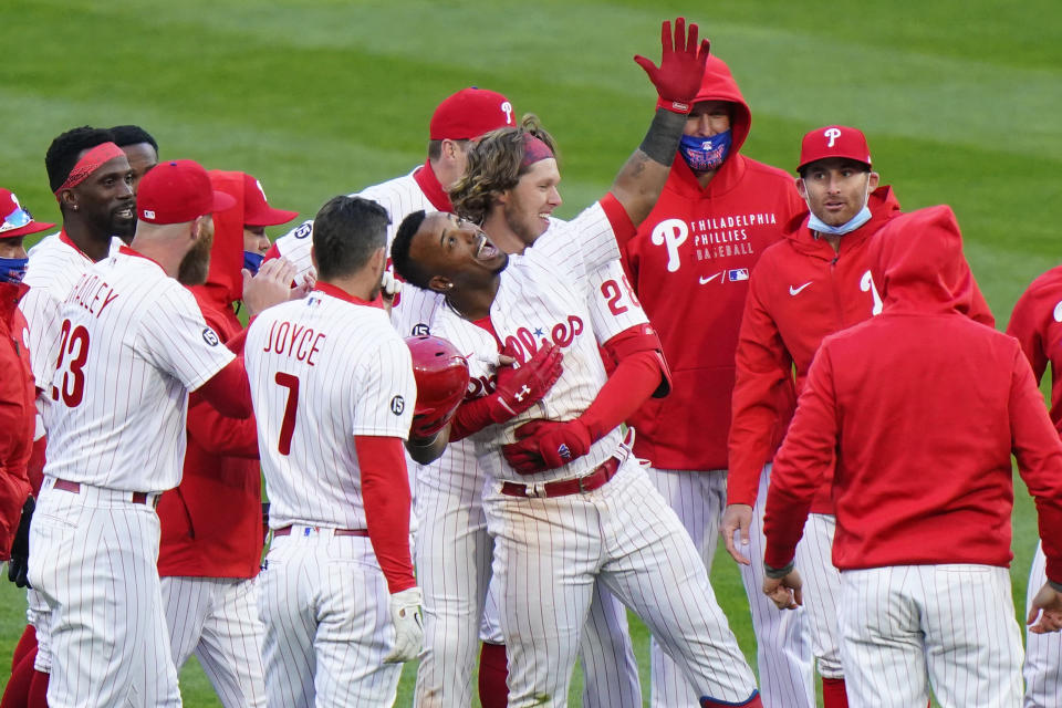 Philadelphia Phillies' Jean Segura, center, celebrates with teammates after hitting a game-winning RBI-single off Atlanta Braves relief pitcher Nate Jones during the 10th inning of an opening day baseball game, Thursday, April 1, 2021, in Philadelphia. (AP Photo/Matt Slocum)