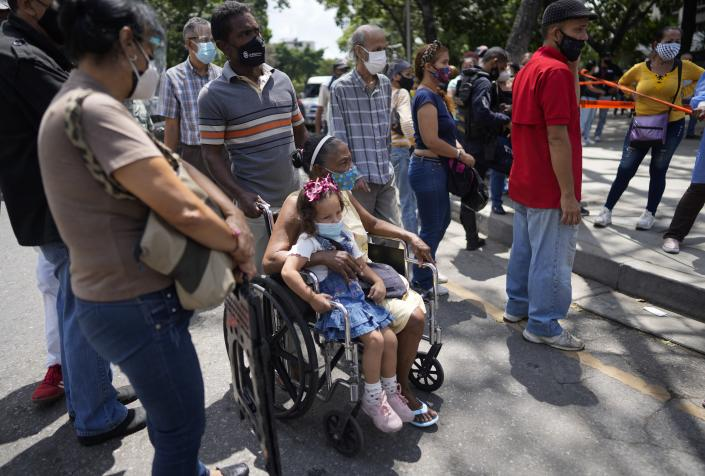 Residents gather outside a vaccination center looking to be inoculated with a second dose of the Sputnik V COVID-19 vaccine, in Caracas, Venezuela, Thursday, Sept. 16, 2021. The Venezuelan government is beginning rollouts of second doses following months of delays. (AP Photo/Ariana Cubillos)