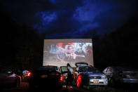"""FILE - In this Friday, May 15, 2020, file photo, guests watch a showing of """"Trolls World Tour,"""" at the Four Brothers Drive In Theatre amid the coronavirus pandemic, in Amenia, N.Y. Most North American theaters weren't open for six months straight through the summer season, which typically accounts for around 40% of the year's profits. For the past two years, the summer movie season has netted over $4.3 billion. This year it brought in $176.5 million, much of that from drive-in theaters. (AP Photo/John Minchillo, File)"""