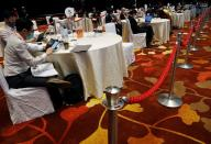 Attendees sit apart at socially distanced tables segregated by ropes during a conference held by the Institute of Policy Studies at Marina Bay Sands Convention Centre in Singapore