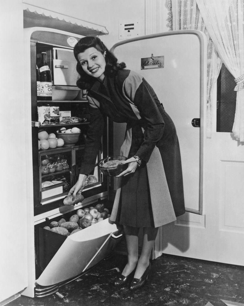 <p>The <em>Gilda </em>actress shows off a packed refrigerator and pulls a potato from the bottom drawer while making dinner in 1941. </p>