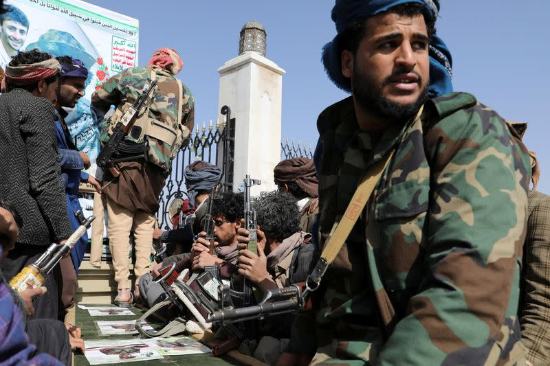 Armed Houthi followers sit next to a coffin of a Houthi fighter killed in recent fighting against government forces in Yemen's oil-rich province of Marib, following a funeral procession in Sanaa