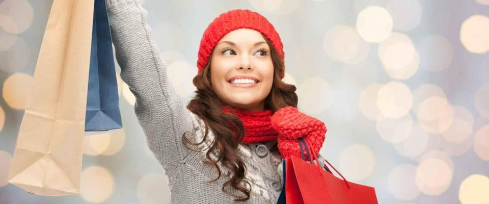 happy young woman in winter clothes with shopping bags over lights background