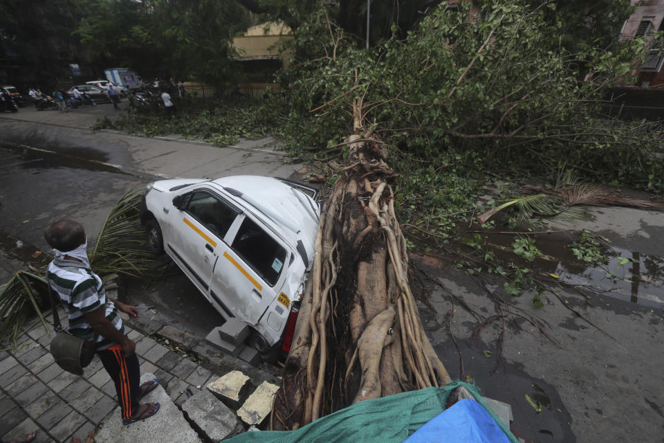 A car stands damaged with a fallen tree after heavy rainfall in Mumbai India, Tuesday, May 18, 2021. The Maharashtra state capital was largely spared from any major damage as Cyclone Tauktae, the most powerful storm to hit the region in more than two decades, came ashore in neighboring Gujarat state late Monday. (AP Photo/Rafiq Maqbool)