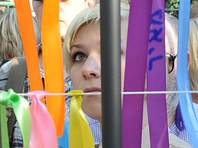 A woman looks at ribbons with Jewish names hung on the fence of a former Jewish orphanage, in Warsaw, Poland, Sunday, July 22, 2012, during commemorations marking the 70th anniversary of first transport of Jews from the Warsaw Ghetto to the Treblinka death camp during World War II. ( AP Photo/Alik Keplicz)