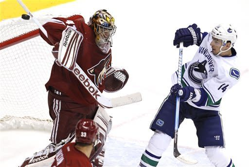 Phoenix Coyotes' Mike Smith makes a stick save on a deflected shot by Vancouver Canucks' Alex Burrows (14) during the first period in an NHL hockey game, Tuesday, Feb. 28, 2012, in Glendale, Ariz. (AP Photo/Ross D. Franklin)