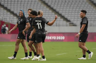 New Zealand players, including Sione Molia, left, celebrate as they walk off the pitch after defeating Argentina in men's rugby sevens match at the 2020 Summer Olympics, Monday, July 26, 2021 in Tokyo, Japan. (AP Photo/Shuji Kajiyama)