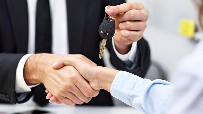 Car salesman shakes hand and gives car keys to woman car buyer