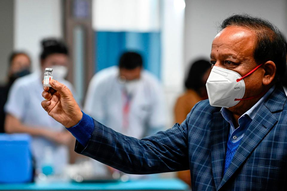 File: Harsh Vardhan displays a vial of a Covid-19 vaccine at the All India Institute of Medical Sciences in Delhi on 16 January 2021 (AFP via Getty Images)