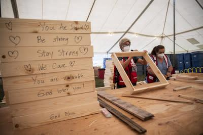A volunteer working in partnership with the American Red Cross writes words of support on sifters. These sifters will be used to salvage items remaining at burned homes in the Silverton, Oregon area. (Photo by Scott Dalton/American Red Cross)