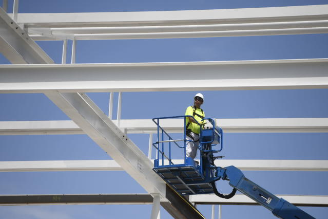 In this July 3, 2018, file photo, a construction worker lowers himself on a forklift at a construction site in Chicago. On Tuesday, Aug. 4, the Commerce Department reports on U.S. construction spending in July. (AP Photo/Annie Rice)