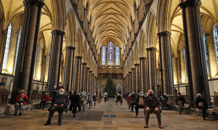 People sit and relax after receiving their Pfizer-BioNTech vaccination at Salisbury Cathedral in Salisbury, England, Wednesday, Jan. 20, 2021. Salisbury Cathedral opened its doors for the second time as a venue for the Sarum South Primary Care Network COVID-19 Local Vaccination Service. (AP Photo/Frank Augstein)