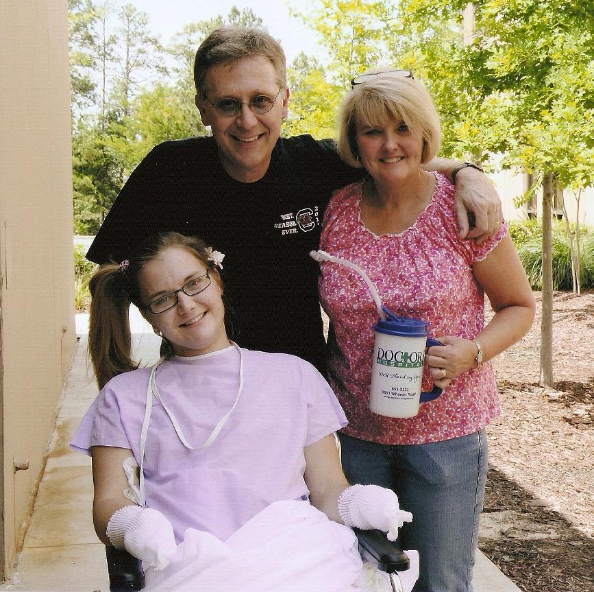 FILE - In this Saturday, June 23 2012 file photo provided by the Copeland family, Aimee Copeland, left, poses with her parents, Andy and Donna Copeland, outside Doctors Hospital in Augusta, Ga. Aimee Copeland was released from Doctors Hospital on Monday, July 2, 2012. She will move to an inpatient rehabilitation clinic and spend the next several weeks learning to move herself with the aid of a wheelchair after having her left leg, right foot and both hands amputated. (AP Photo/Copeland Family, File)