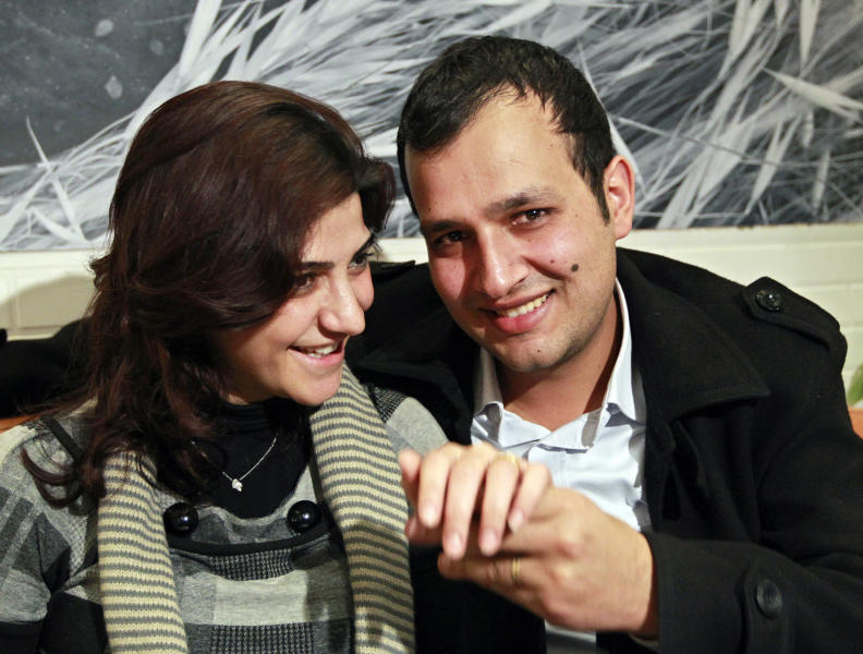 In this picture taken on Wednesday, Jan. 30, 2013, Lebanese couple Kholoud Sukkarieh, left, and her husband Nidal Darwish, right, pose during an interview with the Associated Press, in Beirut, Lebanon. She was an English language tutor with an easy smile and an independent streak. He was a gym receptionist who wanted to better himself. They met for English lessons, swapped views on life and fell in love. Three months ago, a notary married them before their friends and family _ but not in the eyes of the Lebanese government. The would-be marriage of Kholoud Sukkarieh and Nidal Darwish _ which the government has not recognized because a religious official did not register it _ has sparked a fierce debate in Lebanon over civil marriage and how its legalization would affect the country's tenuous sectarian system. (AP Photo/Bilal Hussein)