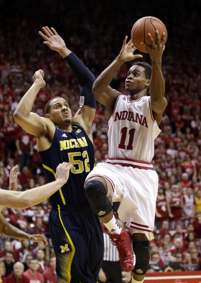 Indiana guard Yogi Ferrell, right, shoots a basket over Michigan forward Jordan Morgan in the second half of an NCAA college basketball game in Bloomington, Ind., Sunday, Feb. 2, 2014. Indiana defeated Michigan 63-52. (AP Photo/Michael Conroy)