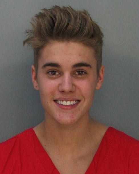 Justin Bieber smiles in his 2014 mugshot after he was arrested in Miami Beach, Florida. (Photo by Miami-Dade Police Department/Sipa USA)