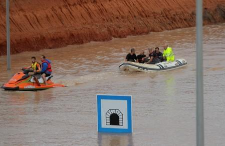 Rescue workers on a boat rescue a person who was stranded inside a flooded tunnel after heavy floods in Pilar de la Horadada