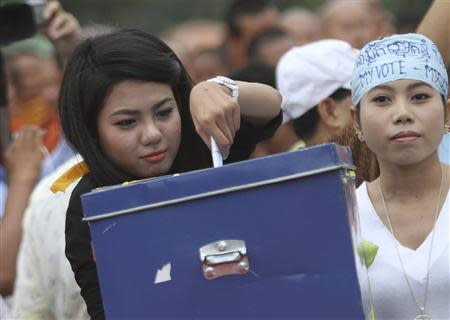 A youth volunteer of the Cambodian National Rescue Party slots in money into a box during a rehearsal of a demonstration ahead of the planned September 8 mass protests, in Phnom Penh