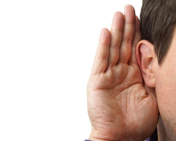 Man with hand cupped on ear