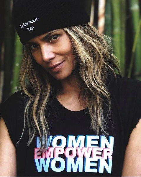 """Halle Berry wearing a black beanie that says """"woman up"""" and a black shirt that says """"women empower women"""" in blue, pink and white lettering"""