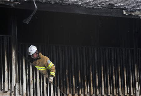 A firefighter climbs a staircase to the second floor of the charred remains of the Mariner's Cove Inn in Point Pleasant Beach, New Jersey, March 21, 2014. REUTERS/Charles Mostoller