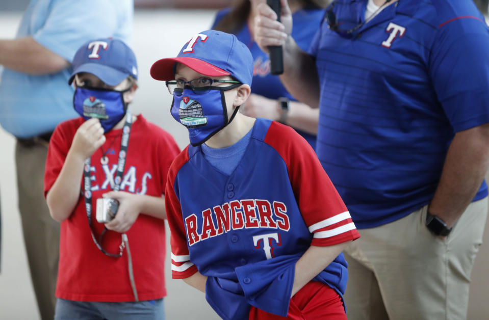 Gavin Bollmer, left, and his buddy, Austin LaFountain, wear masks as they tour Globe Life Field, home of the Texas Rangers baseball team, on the first day of public tours in Arlington, Texas, Monday, June 1, 2020. The robust TV experience available to sports fans has caused a decline in ticket sales for years, and now the coronavirus pandemic is forcing leagues to have games without them at all. But once they are allowed back in the stadium, ensuring fans are safe while also being entertained will be of paramount importance. (AP Photo/LM Otero, File)