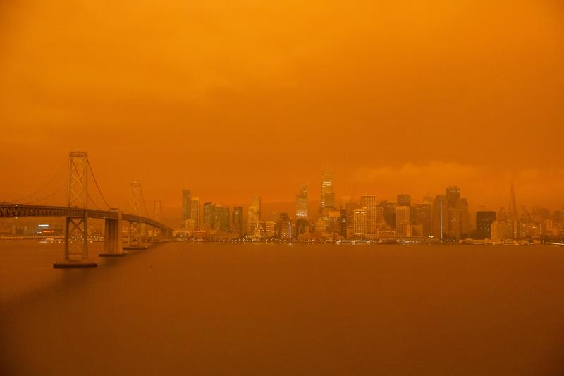 The San Francisco Bay Bridge and city skyline are obscured in orange smoke and haze.