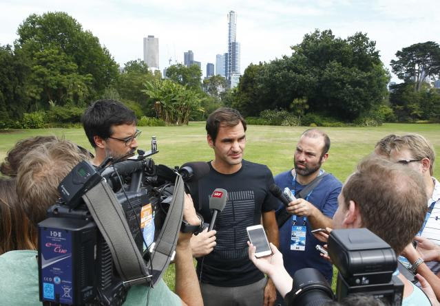Tennis - Australian Open - Melbourne, Australia, January 29, 2018. Roger Federer of Switzerland is surrounded by members of the media during the men's singles winner's photoshoot at the government house in Melbourne, Australia. REUTERS/Edgar Su