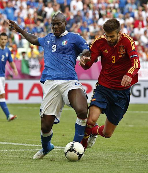 Italy's Mario Balotelli, left, and Spain's Gerard Pique fight for the ball during the Euro 2012 soccer championship Group C match between Spain and Italy in Gdansk, Poland, Sunday, June 10, 2012. (AP Photo/Matt Dunham)