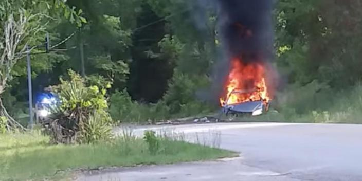 A screenshot from a Facebook video showing a burning car on the side of a wooded road.