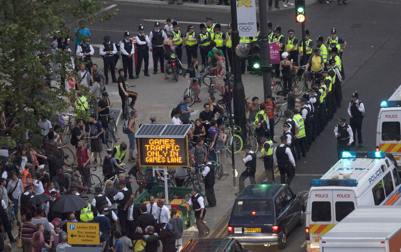 Police surround part of a group of protesting cyclists who tried to block traffic with a mass cycle ride on a road outside the Olympic Park during the Opening Ceremony of the 2012 Summer Olympics, Friday, July 27, 2012, in London. (AP Photo/Ben Curtis)