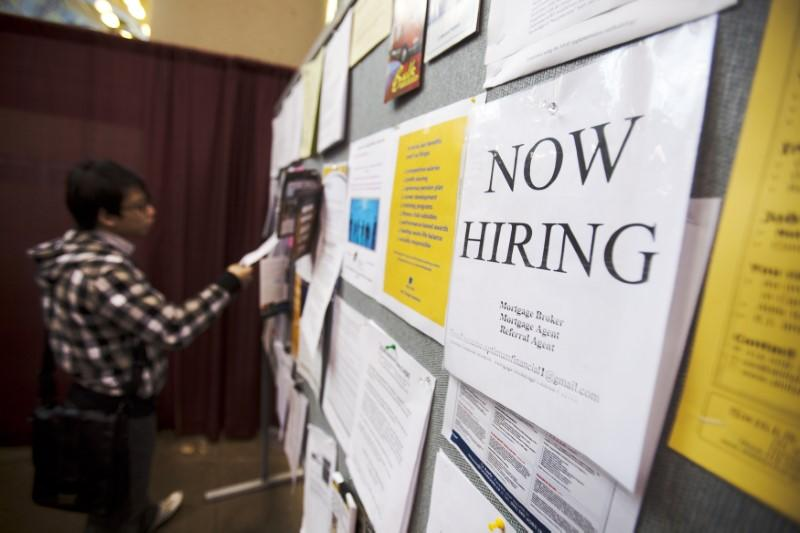 A man looks at a job board posted at a job fair in Toronto, April 1, 2009. REUTERS/Mark Blinch (CANADA BUSINESS) - RTXDID0