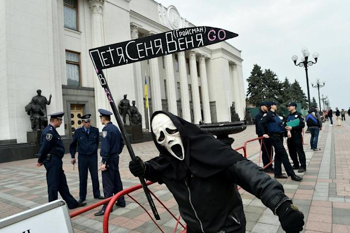 """A man dressed up as the Grim Reaper holds a scythe reading """"Petro, Arseniy and Volodymyr go"""" during a protest in front of parliament in Kiev on April 11, 2016 (AFP Photo/Sergei Supinsky)"""