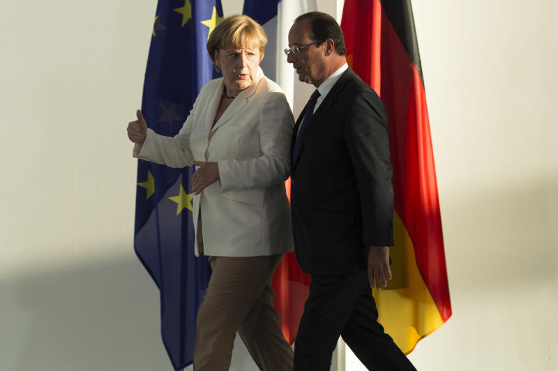 Germany's Chancellor Angela Merkel, left, and France's President Francois Hollande arrive for a statement prior to a meeting at the chancellery in Berlin, Thursday, Aug. 23, 2012. The leaders of Germany and France are stressing that it's up to Greece to keep pursuing painful reforms as it strives to keep its place in the euro. Chancellor Angela Merkel and President Francois Hollande met on Thursday before both hold talks over the next two days with Greece's new prime minister, Antonis Samaras. (AP Photo/Markus Schreiber)