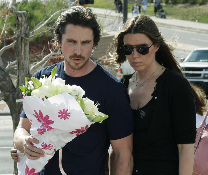 """Actor Christian Bale and his wife Sibi Blazic carry flowers to place on a memorial to the victims of Friday's mass shooting, Tuesday, July 24, 2012, in Aurora, Colo. Twelve people were killed when a gunman opened fire during a late-night showing of the movie """"The Dark Knight Rises,"""" which stars Bale as Batman. (AP Photo/Ted S. Warren)"""