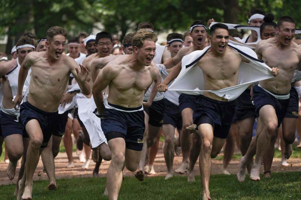 Midshipmen 4th Class from the 14th Company rip their shirts as they run toward the Herndon Monument during the Herndon Monument Climb at the U.S. Naval Academy, Saturday, May 22, 2021, in Annapolis, Md. Freshmen, known as Plebes, participate in the climb to celebrate finishing their first year at the academy. The climb, which took 3:41 hours to complete, was reached when Midshipman 4th Class Michael Lancaster, 19, center, of Signal Hill, Tenn., of the 14th Company, placed a cover atop the monument. (AP Photo/Julio Cortez)