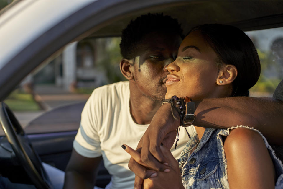 Young couple sitting car, kissing