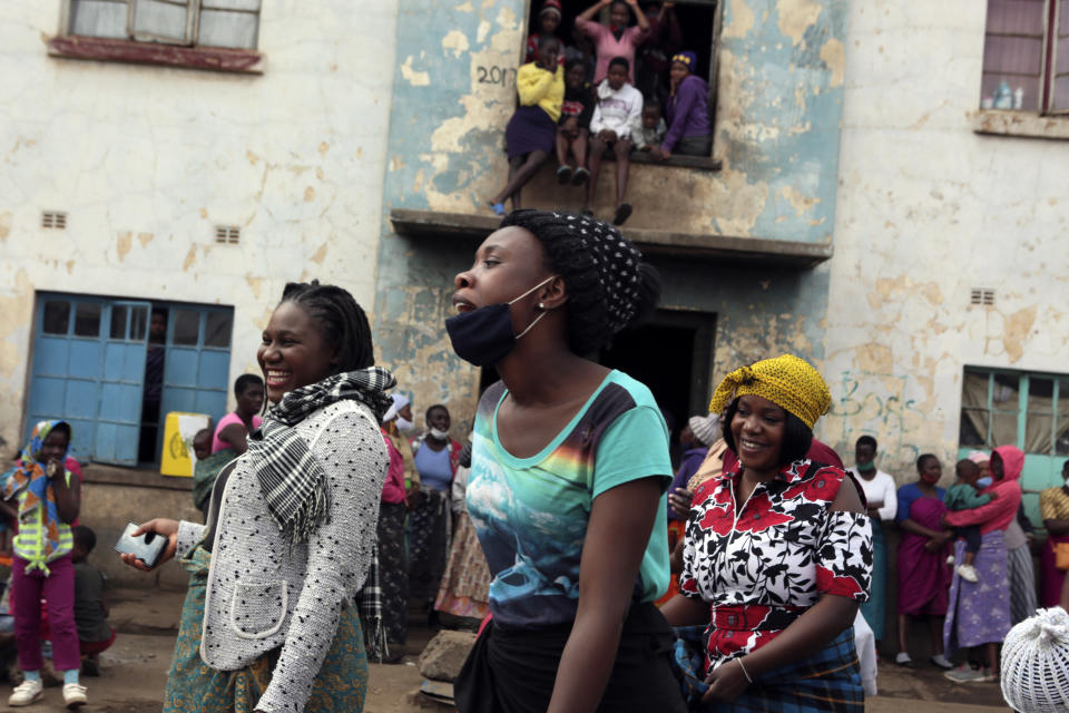 Women share a light moment while attending a social gathering in a poor neighbourhood in Mbare, Harare, Friday, Sept,18, 2020. As Zimbabwe's coronavirus infections decline, strict lockdowns designed to curb the disease are being replaced by a return to relatively normal life. The threat has eased so much that many people see no need to be cautious, which has invited complacency. (AP Photo/Tsvangirayi Mukwazhi)