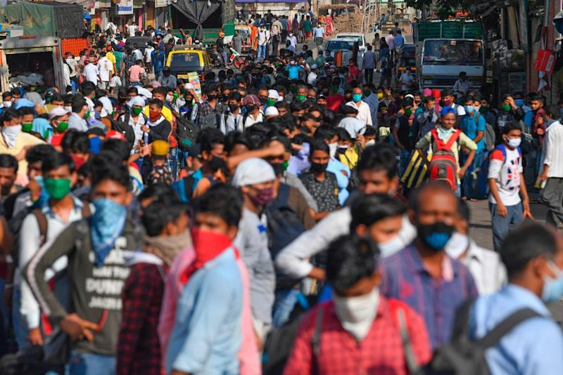 Migrant workers gather outside Dharavi slums to board a bus in Mumbai on May 12. Source: Getty