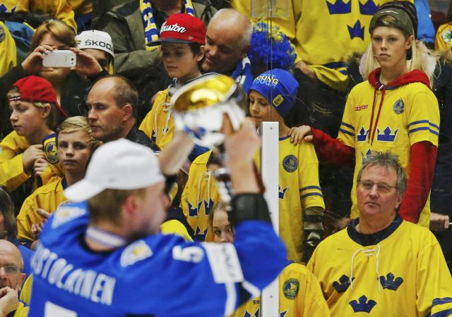 Swedish fans watch Finland's Rasmus Ristolainen celebrates with the trophy after defeating Sweden in overtime of their IIHF World Junior Championship gold medal ice hockey game in Malmo, Sweden, January 5, 2014. REUTERS/Alexander Demianchuk (SWEDEN - Tags: SPORT ICE HOCKEY)